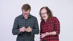 Ανώτερο άτομο hipster που παίρνει στο νέο άτομο hipster που χρησιμοποιεί το τηλέφωνο απόθεμα βίντεο