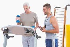 Ανώτερο άτομο treadmill με τον εκπαιδευτή Στοκ εικόνα με δικαίωμα ελεύθερης χρήσης