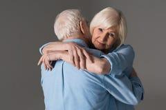 Ανώτερο αγκάλιασμα ζευγών που απομονώνεται στο γκρι στο στούντιο Στοκ Φωτογραφία