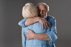Ανώτερο αγκάλιασμα ζευγών που απομονώνεται στο γκρι στο στούντιο Στοκ Εικόνες