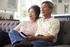 Ανώτερο ασιατικό ζεύγος στο σπίτι στον καναπέ που προσέχει τη TV από κοινού Στοκ Φωτογραφία