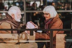 Ανώτερο γενειοφόρο άτομο που δίνει το συμπαθητικό παρόν στη σύζυγό του στοκ φωτογραφίες με δικαίωμα ελεύθερης χρήσης