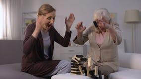 Ανώτερο γυναικών παιχνίδι φραγμών γέλιου παίζοντας και σπάζοντας πύργος, ευτυχής αποχώρηση απόθεμα βίντεο