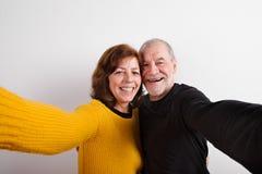 Ανώτερο ερωτευμένο αγκάλιασμα ζευγών, που παίρνει selfie όμορφες νεολαίες γυναικών στούντιο ζευγών χορεύοντας καλυμμένες Στοκ Εικόνα