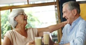 Ανώτερο ζεύγος με τις κούπες καφέ που γελούν και που αγκαλιάζουν 4k απόθεμα βίντεο