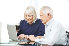 Ανώτερο ζεύγος με τον υπολογιστή που κάνει σερφ το Διαδίκτυο Στοκ εικόνες με δικαίωμα ελεύθερης χρήσης