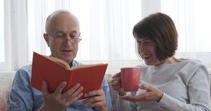 Ανώτερο ζεύγος που έχει το βιβλίο ανάγνωσης διασκέδασης στο σπίτι φιλμ μικρού μήκους