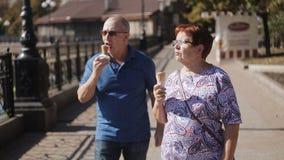 Ανώτερο ζεύγος που έχει το παγωτό στον περίπατο μια ηλιόλουστη ημέρα φιλμ μικρού μήκους