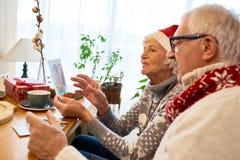 Ανώτερο ζεύγος που εξετάζει τις φωτογραφίες στα Χριστούγεννα στοκ εικόνες