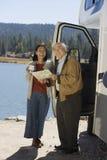 Ανώτερο ζεύγος που εξετάζει το χάρτη έξω από το rv στη λίμνη Στοκ Φωτογραφία