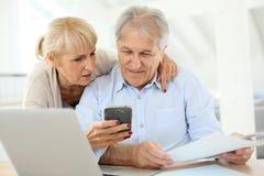 Ανώτερο ζεύγος που εργάζεται στο lap-top και το smartphone στοκ φωτογραφίες