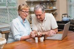 Ανώτερο ζεύγος που κοιτάζει επάνω στο φάρμακο on-line στοκ εικόνα