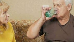 Ανώτερο ζεύγος που παίρνει τα χάπια στο σπίτι Το αρσενικό υπερβολικό βάρος παίρνει ένα χάπι, η γυναίκα παίρνει ένα ποτήρι του νερ φιλμ μικρού μήκους