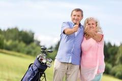 Ανώτερο ζεύγος που παρουσιάζει ΕΝΤΑΞΕΙ σημάδι σε ένα γήπεδο του γκολφ Στοκ φωτογραφία με δικαίωμα ελεύθερης χρήσης