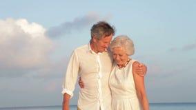 Ανώτερο ζεύγος που περπατά στην όμορφη παραλία φιλμ μικρού μήκους