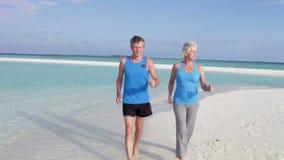 Ανώτερο ζεύγος που περπατά στην όμορφη παραλία απόθεμα βίντεο