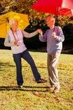 Ανώτερο ζεύγος που χορεύει με τις ομπρέλες Στοκ εικόνα με δικαίωμα ελεύθερης χρήσης