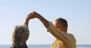 Ανώτερο ζεύγος που χορεύει στον περίπατο κοντά στην παραλία 4k