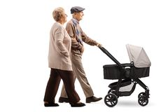 Ανώτερο ζεύγος που ωθεί έναν περιπατητή μωρών στοκ εικόνα με δικαίωμα ελεύθερης χρήσης