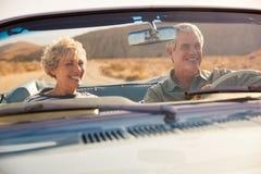 Ανώτερο ζεύγος σε ένα αμερικανικό οδικό ταξίδι, που βλέπει μέσω του αλεξήνεμου αυτοκινήτων στοκ εικόνες με δικαίωμα ελεύθερης χρήσης