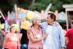 Ανώτερο ζεύγος στην έκθεση διασκέδασης, αγκάλιασμα καλοκαίρι ηλιόλουστο Στοκ Εικόνες