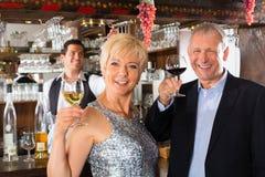 Ανώτερο ζεύγος στη ράβδο με το ποτήρι του κρασιού στη διάθεση Στοκ εικόνες με δικαίωμα ελεύθερης χρήσης