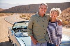 Ανώτερο ζεύγος στο οδικό ταξίδι που υπερασπίζεται το αυτοκίνητο που χαμογελά στη κάμερα στοκ εικόνες
