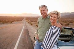 Ανώτερο ζεύγος στο οδικό ταξίδι που υπερασπίζεται το αυτοκίνητο που χαμογελά στη κάμερα στοκ εικόνα