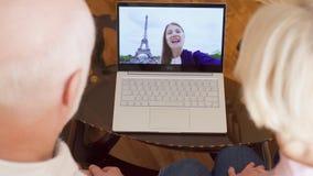 Ανώτερο ζεύγος στο σπίτι που έχει την τηλεοπτική συνομιλία με την κόρη σπουδαστών από το Παρίσι, πύργος του Άιφελ στο υπόβαθρο απόθεμα βίντεο