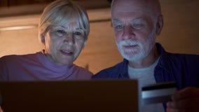 Ανώτερο ζεύγος στο σπίτι στην κουζίνα τη νύχτα Συνταξιούχος οικογένεια που ψωνίζει on-line με την πιστωτική κάρτα στο lap-top φιλμ μικρού μήκους