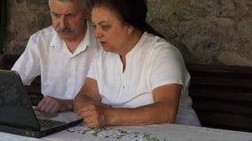 Ανώτερο ζεύγος Eldery σε έναν πάγκο με το lap-top απόθεμα βίντεο