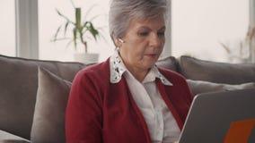 Ανώτερο θηλυκό freelancer που εργάζεται το γραφείο στο ψηφιακό πρόγραμμα φιλμ μικρού μήκους