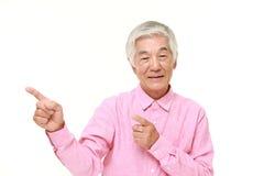 Ανώτερο ιαπωνικό άτομο που παρουσιάζει και που παρουσιάζει κάτι Στοκ Εικόνα