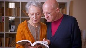 Ανώτερο καυκάσιο ζεύγος στο βιβλίο ανάγνωσης TV μαζί στη βιβλιοθήκη φιλμ μικρού μήκους