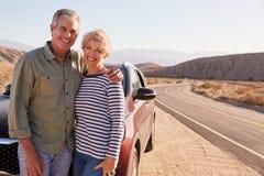 Ανώτερο λευκό ζεύγος που στέκεται στην άκρη του δρόμου ερήμων με το αυτοκίνητο στοκ φωτογραφία με δικαίωμα ελεύθερης χρήσης