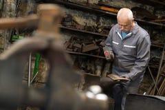 Ανώτερο μέταλλο σφυρηλατημένων κομματιών σιδηρουργών στο αμόνι στο σιδηρουργείο Στοκ εικόνες με δικαίωμα ελεύθερης χρήσης