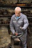 Ανώτερο μέταλλο σφυρηλατημένων κομματιών σιδηρουργών στο αμόνι Στοκ Εικόνες