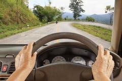 Ανώτερο οδηγώντας αυτοκίνητο γυναικών στο δρόμο βουνών Στοκ Φωτογραφία