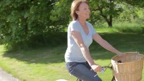 Ανώτερο οδηγώντας ποδήλατο γυναικών κατά μήκος της διαδρομής χώρας απόθεμα βίντεο