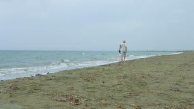 Ανώτερο παντρεμένο ζευγάρι που απολαμβάνει τον περίπατο κατά μήκος της παραλίας Ταξίδι συνταξιούχων φιλμ μικρού μήκους