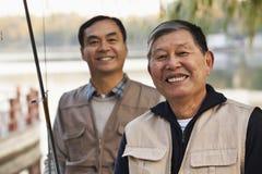 Ανώτερο πορτρέτο φίλων αλιεύοντας σε μια λίμνη Στοκ Εικόνες