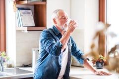 Ανώτερο πόσιμο νερό ατόμων στην κουζίνα Στοκ εικόνα με δικαίωμα ελεύθερης χρήσης
