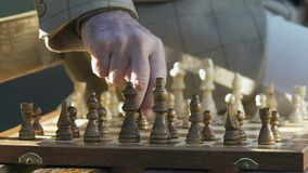 Ανώτερο σκάκι παιχνιδιού ατόμων στον πάγκο πάρκων, κινούμενοι εκλεκτής ποιότητας αριθμοί εν πλω, χόμπι απόθεμα βίντεο
