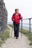 Ανώτερο σκανδιναβικό περπάτημα γυναικών στο δύσκολο ίχνος στοκ φωτογραφία