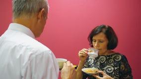 Ανώτερο τσάι κατανάλωσης ζευγών με το μπισκότο και ομιλία Τρόπος ζωής ηλικιωμένων ανθρώπων απόθεμα βίντεο