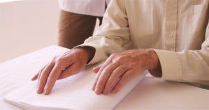 Ανώτερο τυφλό άτομο που διαβάζει ένα βιβλίο μπράιγ φιλμ μικρού μήκους