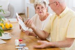 Ανώτερο φυλλάδιο ανάγνωσης γυναικών ενός φαρμάκου και μιας ηλικιωμένης εκμετάλλευσης π ανδρών στοκ εικόνες