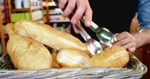 Ανδρικό προσωπικό που τακτοποιεί μια φραντζόλα του ψωμιού στο ψάθινο καλάθι απόθεμα βίντεο