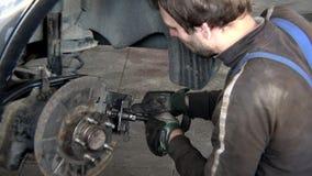 Ανδρικό σύστημα φρένων αυτοκινήτων επισκευής εργαζομένων γκαράζ στην εργασία φιλμ μικρού μήκους