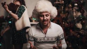 Αοιδός στο τραγούδι καπέλων γουνών με τη συνεδρίαση κουαρτέτων σειράς κοντά στο χριστουγεννιάτικο δέντρο απόθεμα βίντεο